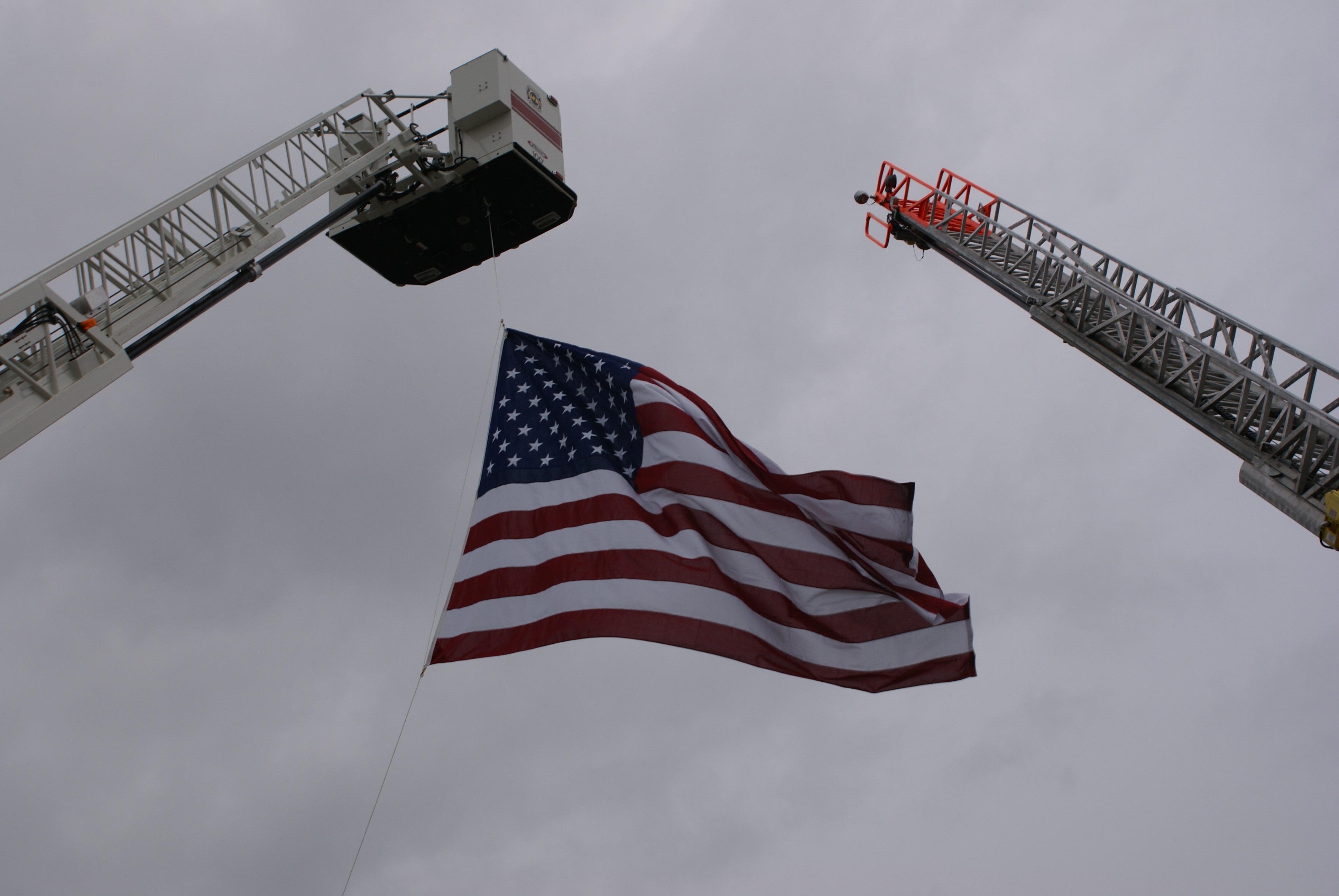 American Flag Hanging from Fire Truck Ladders